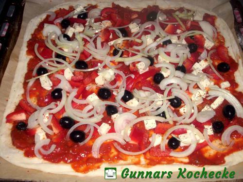 Tomatensauce, Feta, Oliven, Paprika und Zwiebeln auf dem Teig verteilen