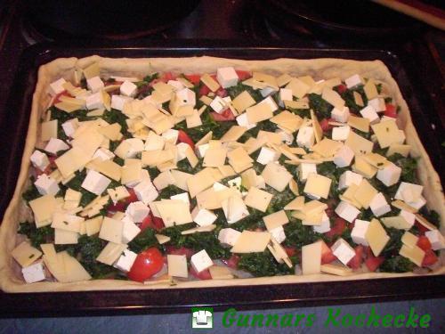 Spinat, Tomaten, Feta und Gouda auf dem Teig verteilen
