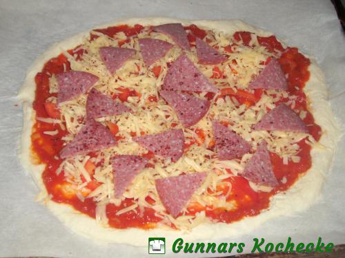 Pizza mit Paprika, Käse und Salami belegen